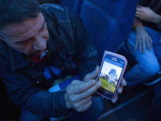 A Syrian refugee shows his home town of Hama on his phone while enroute to Canada. © IOM/Muse Mohammed 2015